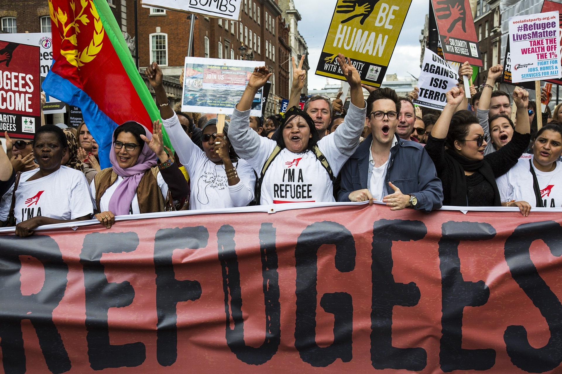 Protesters behind a banner chant as thousands march in central London, declaring that refugees are welcome in the UK Photograph: redorbital/Demotix/Corbis